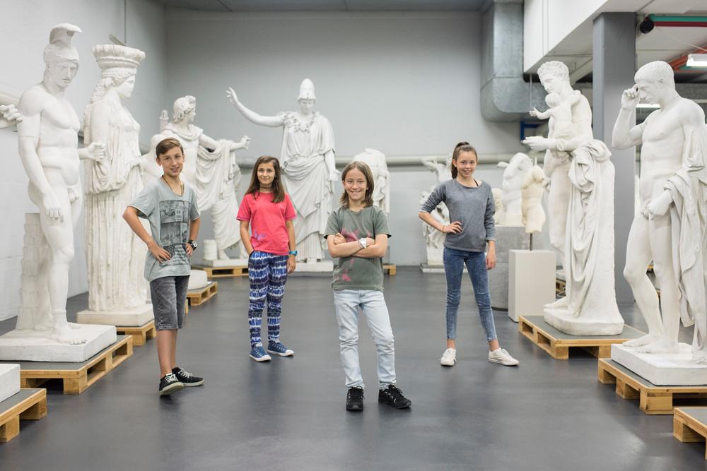Vier Kinder stehen vor Statuen